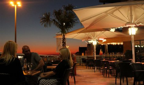 white umbrellas with electric patio heaters at sunset