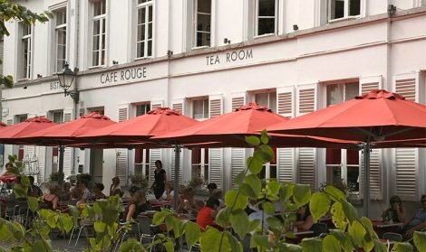 Row of red cafe parasols cover outdoor seating area