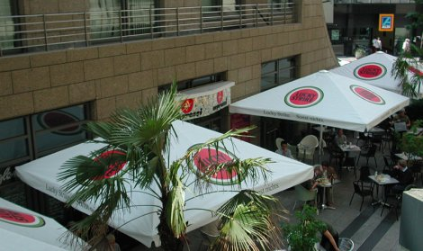 restaurants outside space covered by giant white and red umbrellas