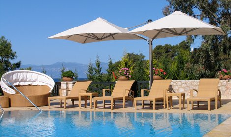 covered outdoor living space with pool and hotel umbrellas