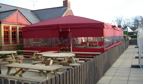 Giant red hotel umbrellas covering wooden tables