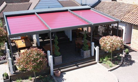 Cafe's covered seating area with red louvred roof